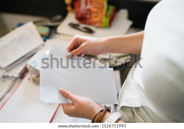Close up on girl female woman hands holding and opening white envelope by the table at office work or at home with bills mail or insurance contract invoice letter
