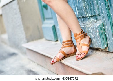 Close up on girl's feet wearing sandals in the city, urban background