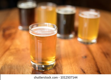 Close up on a glass of India Pale Ale, with a flight of craft beers in the blurry background, at a local brewery