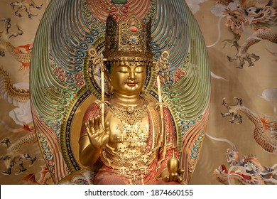 Close up on the golden Buddha statue inside the Buddha Tooth Relic Temple in Chinatown District, Singapore.