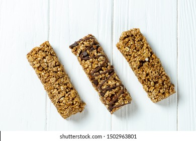 Close up on Granola Bar isolated on white wooden background. Healthy sweet dessert snack. Energy bar of muesli. Granola for breakfast. Copy space