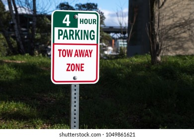 Close up on a green Four Hour Parking sign, above a red Tow Away Zone plaque, along a city street