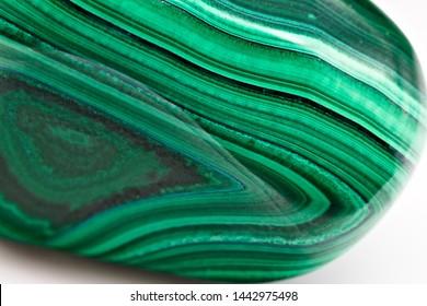 Close up on green polished shiny malachite stone sample isolated on white limbo background