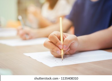 close up on group student hand writing on exam paper (choose choice ) for test graduated , international literacy concept