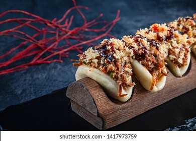 Close up on Gua bao, steamed buns with meat (duck). Bao served with tasty topping on dark background. Asian cuisine. Asian sandwich steamed gua bao. Japanese style fast food