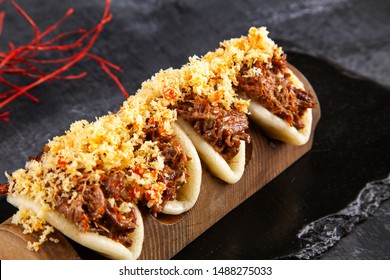 Close up on Gua bao, steamed buns with meat (veel). Bao served with tasty topping on dark background. Asian cuisine. Asian sandwich steamed gua bao. Japanese style fast food. Selective focus