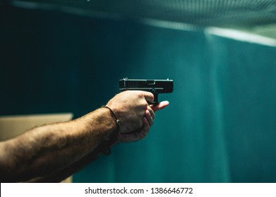 close up on a guy shooting firearm handgun, glock pistol in a firing range