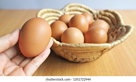 Close up on hand holding egg with basket of eggs in background.