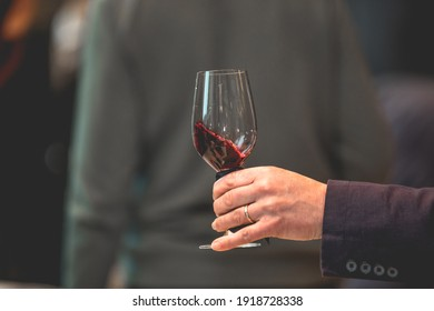 Close up on a hand holding a glass of red wine