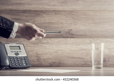 Close up on hand holding pen over paper as symbol of business contract or sales closing concept.