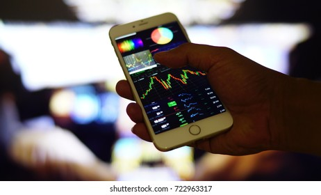 Close up on hand holding smartphone showing graphs and charts on screen with blurred background