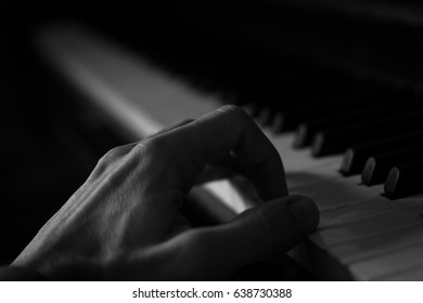 Close up on hand of man playing piano. Black and white photography. Music lessons concept