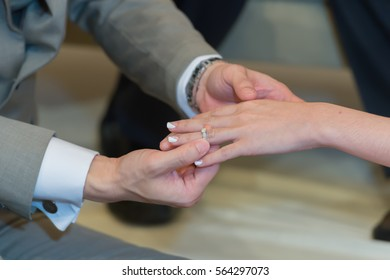 Close up on hand of a man put on an engagement ring on the finger of the bride