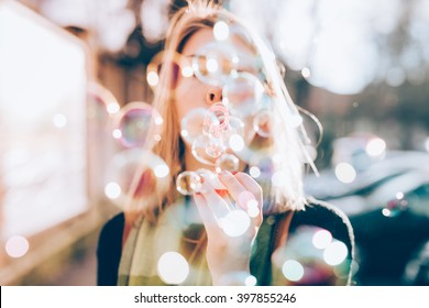 Close up on the hand of young beautiful woman blowing bubble soap - ethereal, joy, happiness concept