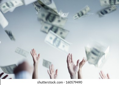 Close up on hands raised throwing and catching money in air