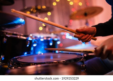 Close up on hands of unknown caucasian woman with drumsticks - unknown female playing drums at night