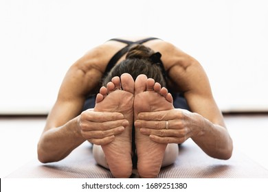 Close up on hands of woman grabbing feet on paschimottanasana c yoga asana. Female yogi on seated forward bend pose at studio over white background. Flexibility, healthy lifestyle concepts