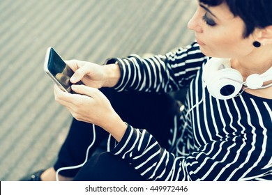Close up on the hands of young beautiful caucasian woman typing on the screen of a smart phone hand hold - texting, technology, social network concept