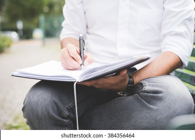 Close up on the hands of a young man writing on his agenda - business, planning, appointment concept