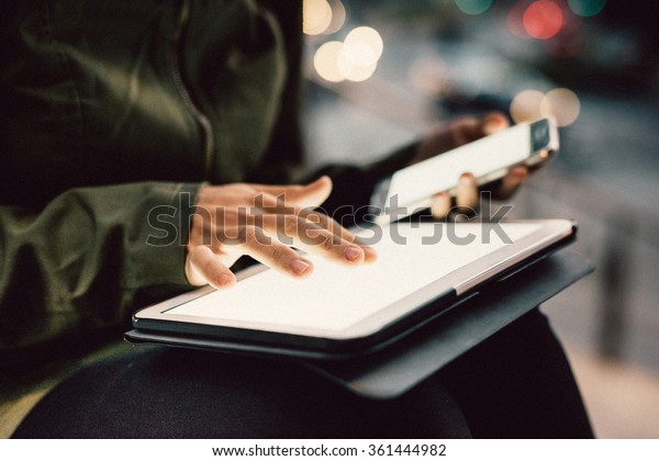 Close up on the hands of young woman using smartphone and tablet in the city night, pointing and touching the screen with her finger - technology, multitasking, communication concept