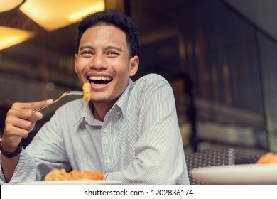 close up on handsome asian man using fork with nugget and try to eating piece of fried chicken at outdoor restaurant on weekend day with chill time, happy lifestyle concept