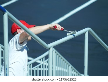 close up on handyman painting the railing outdoor