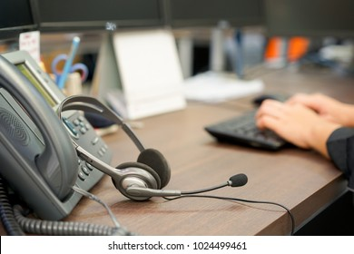 close up on headset of call center leaning on telephone with blur network engineering typing on keyboard for reply case to customer or monitoring alarm , technology concept