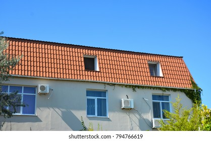 Close up on house with metal roof, mansard, skylight window, air duct,  air conditioner.