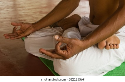 Close up on Indian yoga teacher with white pants in padmasana, known as lotus pose. Hands in chin mudra ready for meditation
