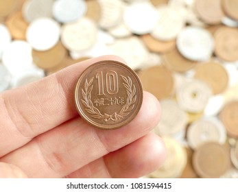 close up on japanese coin (yen) putting on a hand with a background of many kinds of coins