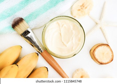 Close up on jar of cosmetic banana facial nourishing mask. Yellow fresh ripe fruit and moisturizer cream, summer replenishing skincare. Light colors.