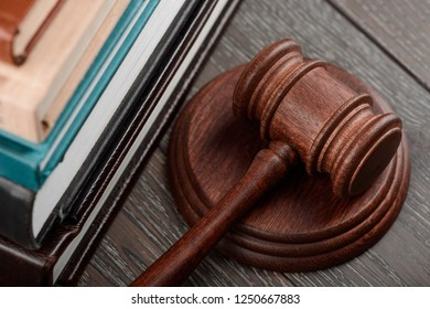 Close up on a judge's gavel and books on wooden table. Juridical system, justice concept.