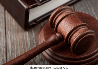 Close up on judge's gavel lying on a sound block and a court book on wooden table. Juridical concept.