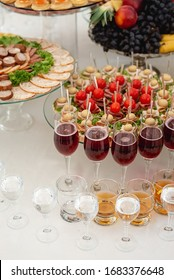 Close up on large selection of food with cold snacks, alcohol, wine glasses, cold meats, cheese. Variety of tasty delicious snacks on the table. Corporate birthday party event or wedding celebration