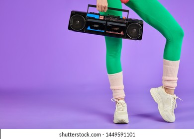 close up on legs and portable radio cassette player, cropped shot of unrecognizable athletic sporty woman standing in green leggins and white training shoes
