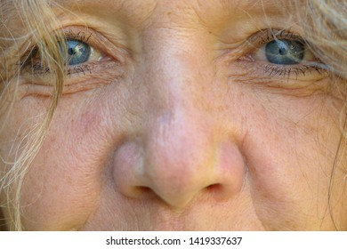 Close up on the lovely blue eyes and nose of a senior woman wearing mascara with wisps of hair framing her face