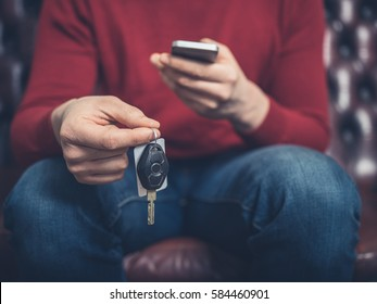 Close up on a man sitting on sofa with a smartphone and car keys