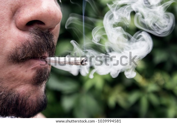 Close up on man smoking cannabis joint.Legal Marijuana / Cannabis Joints for Recreational Use.