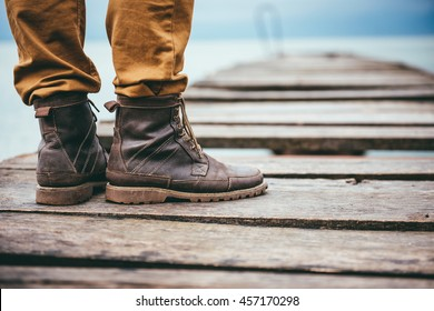 Close up on man standing on dock and wearing leather boots