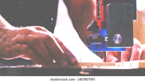 close up on man's hands cutting pieces of wood with Bandsaw in the carpentry workshop