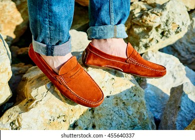 Close up on man's legs wearing red loafers or moccasins on a rocky background in the sun, model posing