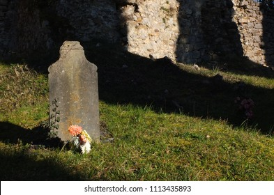 Close up on a medieval tombstone with a pink bouquet in front of it, bathed in gold evening sunlight, Noguès Church, south of France