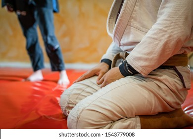 Close up on midsection of the bjj brazilian jiu jitsu athlete sitting on the mats tatami at the training class with hands on his ties wearing white gi kimono