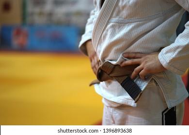 Close up on midsection of a BJJ jiu-jitsu Brazilian jiujitsu Fighter brown belt in a white gi kimono waiting for the fight at the tournament