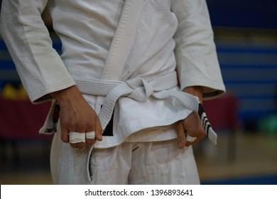 Close up on midsection of a BJJ jiu-jitsu Brazilian jiujitsu Fighter white belt waiting for the fight at the tournament