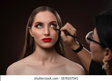 Close up on model. Beautiful model at MUAH artist. Beauty makeup artist working on a fashion model face isolated on black background. Make-up artist, applying eye shadow to the model.