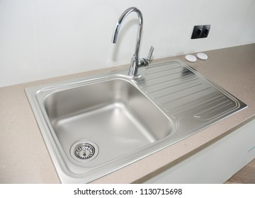 Close up on modern kitchen metal faucet and metal kitchen sink.