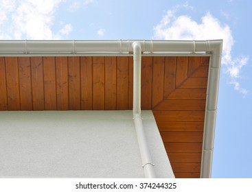 Close up on New Rain Gutter, Downspout,  Soffit Board, Fascia Board Installation Against Blue Sky.