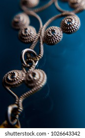 Close up on norwegian traditional silver jewelry on blue background.