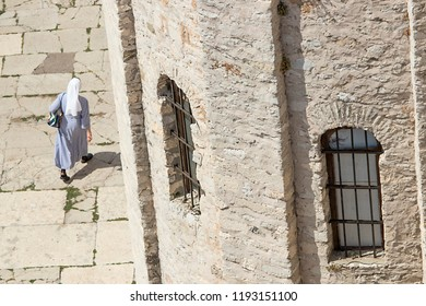 Close up on a nun walking beside a church of st. Donat, a historic monument from the 9th century in Zadar, Croatia  shot from the elevated position